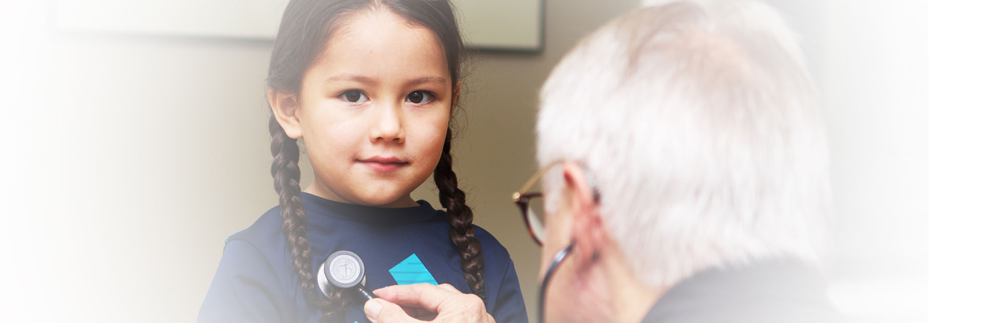 Image of young indigenous girl with doctor holding stethoscope to her heart.