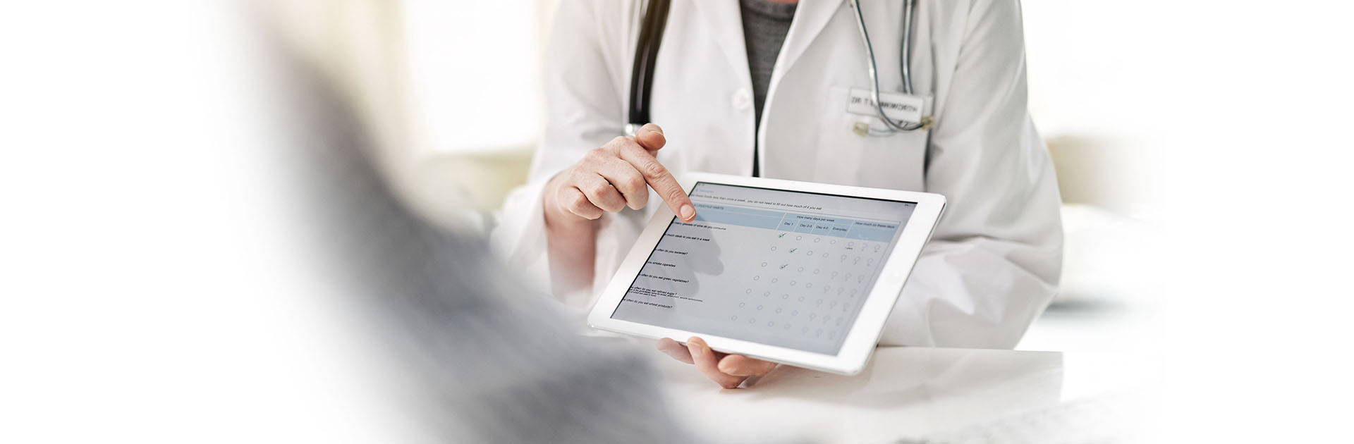 Woman in white coat holding a tablet pointing to the screen